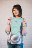 Young pregnant woman with her future baby's clothes Stock Photography