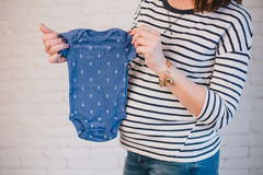 Young pregnant woman with her future baby's clothes Stock Image