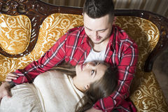 A young pregnant woman and her happy husband resting on the couc Stock Photography
