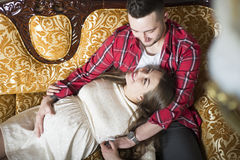 A young pregnant woman and her happy husband resting on the couc Royalty Free Stock Photo