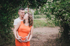 Young pregnant woman with her husband holding hands on her belly Royalty Free Stock Photo