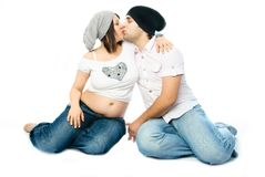 Young pregnant woman and her husband kissing Royalty Free Stock Photos