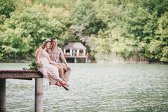 Young pregnant woman with her husband sitting near lake Stock Image