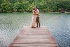 Young pregnant woman with her husband standing near lake Royalty Free Stock Photo