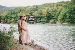 Young pregnant woman with her husband standing near lake Stock Images