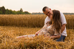 A young pregnant woman with her husband among the wheat field Royalty Free Stock Photo