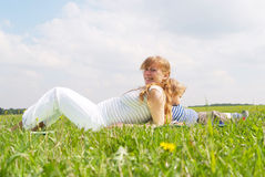 Young pregnant woman with her son. In dandellion field. Spring time royalty free stock photography
