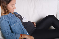 Young pregnant woman holding baby booties on her abdomen. Portrait of beautiful young pregnant woman holding baby booties on her abdomen. Indoors Stock Photography
