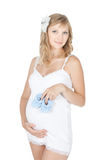 Young pregnant woman holding baby shoes Royalty Free Stock Photography