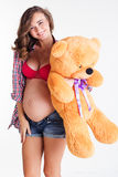 Young pregnant woman is holding teddy bear Royalty Free Stock Photos