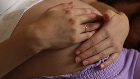 Young pregnant woman holding and touching her belly, closeup. Young pregnant woman holding and touching her belly, close-up stock video