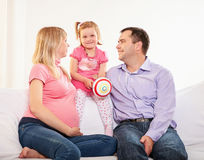 Young pregnant woman, with husband and little daughter Stock Photos