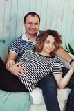Young pregnant woman with husband on white sofa in blue room. Couple dressed in striped t-shirt. Summer inspiration Stock Photos