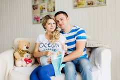 Young pregnant woman and husband on white sofa in room with baby clothes. Royalty Free Stock Photography