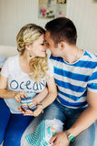 Young pregnant woman with husband on white sofa in room hold baby shoes. Stock Photos