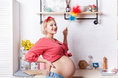 Young pregnant woman iinduces cleanliness in the kitchen with pipidaster. Young pregnant woman induces cleanliness in the kitchen with pipidaster stock images