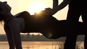 Young Pregnant Woman Keeps Her Belly up , Doing Yoga, at Sunset in 4k stock footage