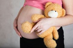 Young pregnant woman keeps plush brown teddy bear. Young pregnant between 30 and 35 years old woman keeps plush brown teddy bear. Closeup royalty free stock image
