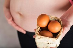 Young pregnant woman keeps woven mini basket with chicken eggs. Young pregnant between 30 and 35 years old woman keeps woven mini basket with chicken eggs stock image