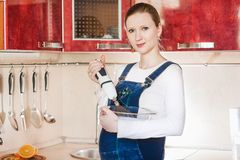 Young pregnant woman in kitchen making a food Stock Photo