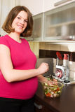 Young pregnant woman in kitchen making salad Stock Photos