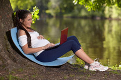 Young pregnant  woman with laptop sits in the park. Royalty Free Stock Image
