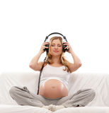 A young pregnant woman listening to the music Stock Images