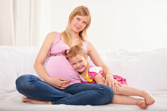 Young pregnant woman with little daughter Royalty Free Stock Photos