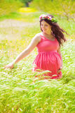 Young pregnant woman with long curly hair in summer Stock Photography