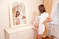 Young pregnant woman looks in a mirror Stock Photography