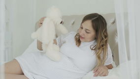 A young pregnant woman lying on the bed and playing with soft toy. stock video