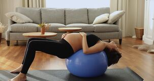Young pregnant woman perform prenatal yoga stretch with stability ball