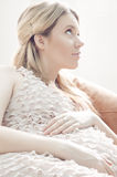 Young pregnant woman in pink dress sitting Stock Image