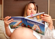 Young pregnant woman reading a  book Royalty Free Stock Image