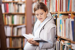 Young pregnant woman reading book stock image