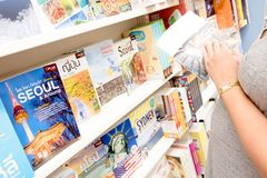Young pregnant woman reading Tokyo travel guide book in bookstore. stock photos