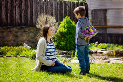 Young pregnant woman, receiving bouquet of colorful flowers from Royalty Free Stock Images
