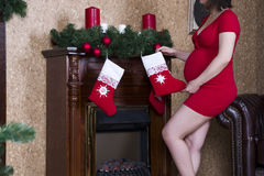 Young pregnant woman in red dress with socks posing on the background of Christmas tree. Holiday concert Royalty Free Stock Photography
