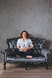 Young pregnant woman with red hair sitting on a gray sofa in the Baroque style. She`s wearing a white shirt, visible to Royalty Free Stock Image