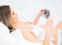 A young pregnant woman relaxing in the bed and holding an ultras Stock Photo