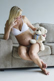 Young pregnant woman relaxing on couch with a teddy bear Royalty Free Stock Photo