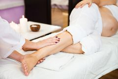 Young pregnant woman relaxing with hand leg massage at beauty sp. Young pregnant woman take relaxing foot massage at beauty spa salon. Close-up. Spa treatment stock photo