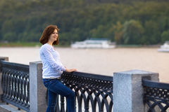 Young pregnant woman relaxing at river shore Stock Image