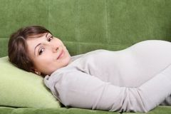 Young pregnant woman relaxing on sofa Royalty Free Stock Images
