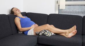Young pregnant woman relaxing on sofa Royalty Free Stock Image