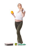 Young  pregnant woman with scales. Royalty Free Stock Images