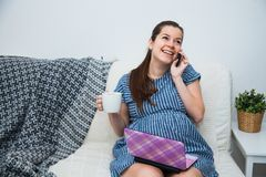 Young pregnant woman shopping online with laptop credit card and smartphone. Preparations before baby birth Stock Image