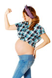 Young pregnant woman showing arm muscles Royalty Free Stock Photo