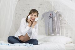 Young pregnant woman. Sit with clothes on white bad in light home badroom stock photography