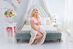 The young pregnant woman sits on a bed Stock Images